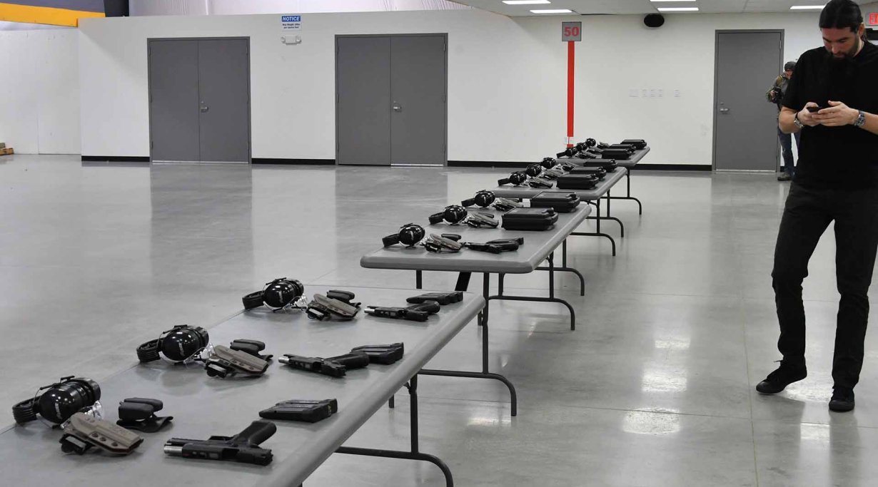 A long table with the SIG Sauer P320 X5 pistols